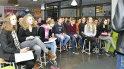 Leerlingen luisteren naar de uitleg over het geven van een goede presentatie over hun ontwerp.